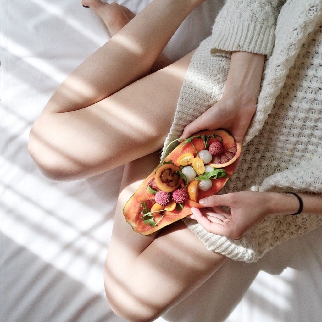 Person holding papaya fruit on bed